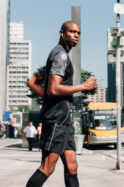 A confident male athlete fit young man jogging on road listening the music on earphone Free Photo