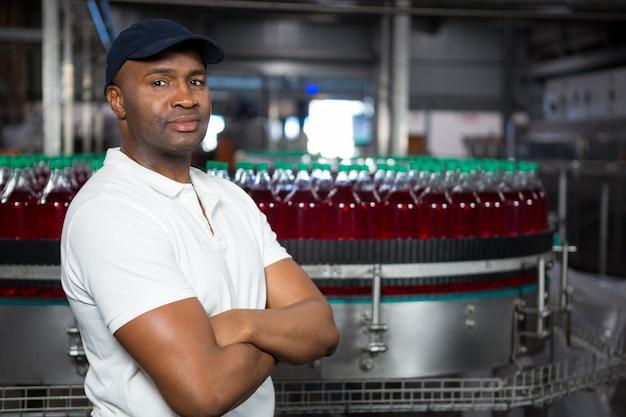 工場で立っている腕を組んで自信を持って男性従業員 無料写真
