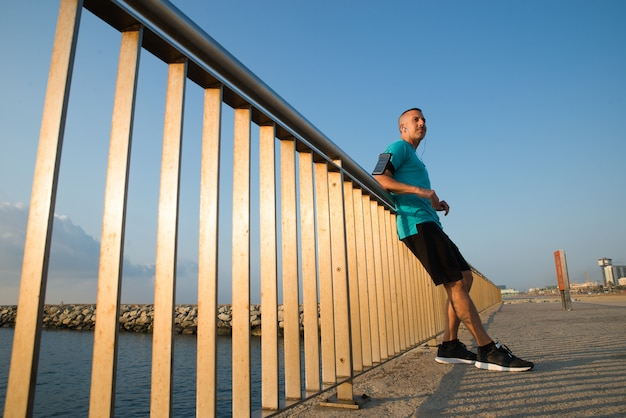 Confident male jogger resting leaning on bridge Free Photo
