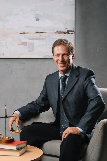 Уверенный мужской зрелый адвокат, сидящий в офисе Бесплатные Фотографии