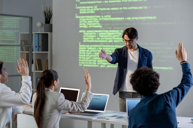 Уверенный учитель-мужчина указывает на одного из студентов в первом ряду, позволяя ей ответить на его вопрос во время презентации Premium Фотографии