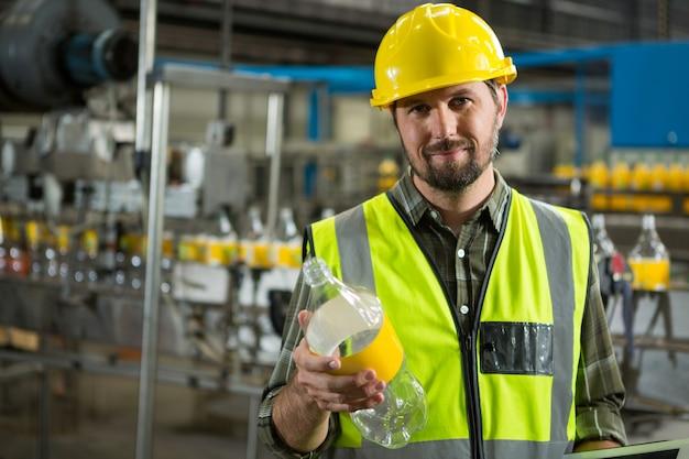 ジュース工場でボトルを検査する自信のある男性労働者 無料写真