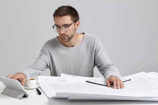 자신감이 남성 노동자는 태블릿 컴퓨터에 세 심하게 보인다, 건설 프로젝트에서 일 무료 사진