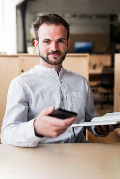 Confident man holding cellphone and diary looking at camera Free Photo