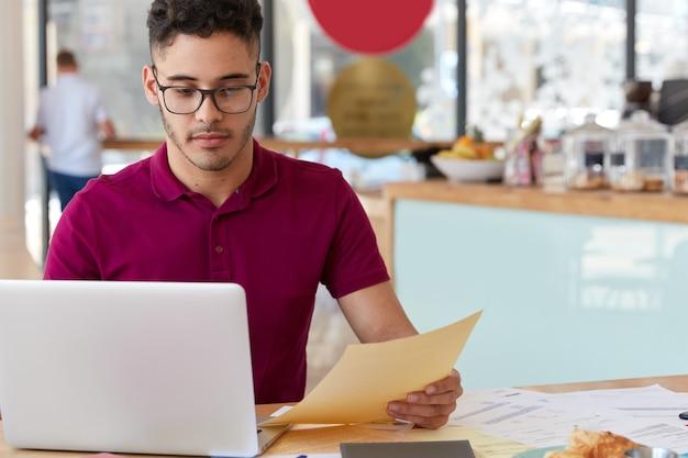캐주얼 복장을 한 자신감 넘치는 남자, 전자 지불 제공, 랩톱 컴퓨터에서 온라인 뱅킹 응용 프로그램 사용, 웹 사이트 페이지 개발, 서류 보유, 아늑한 커피 숍에서 일합니다. 현대 기술 무료 사진