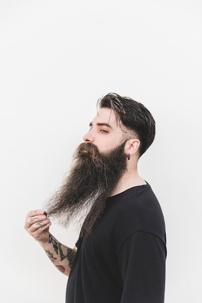 Confident man touching his beard standing against white backdrop Free Photo