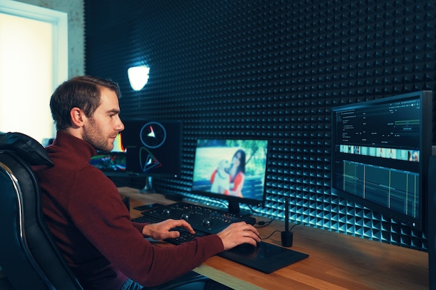 Confident man video editor works with footage in creative office studio. Premium Photo