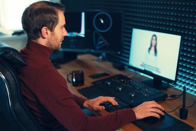 Видеоредактор confident man работает с кадрами в creative office studio. Premium Фотографии