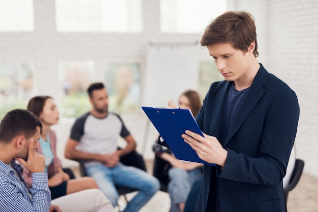 Confident man with blue tablet at group support meeting Premium Photo