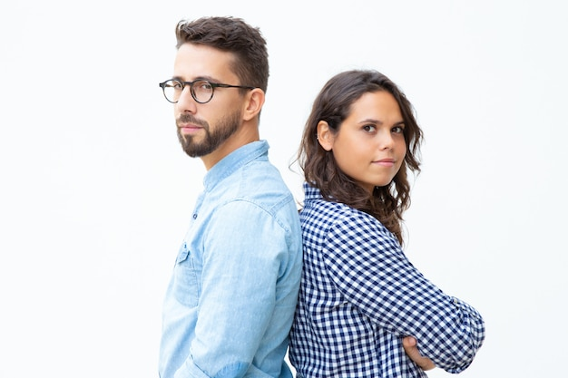 Confident man and woman standing back to back Free Photo