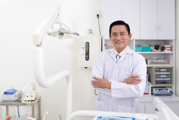 Confident middle-aged asian male dentist posing in clinic Free Photo