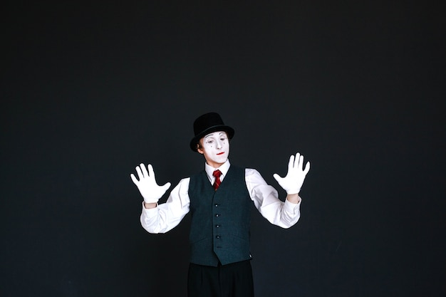 Confident mime holds his palms on invisible wall Free Photo