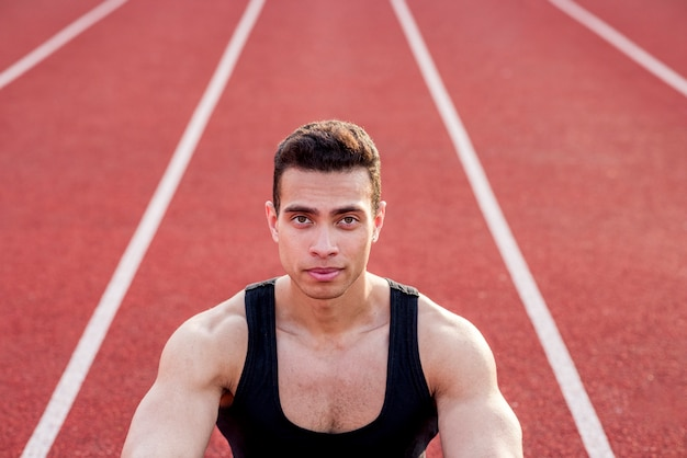 Confident muscular sport person on red race track looking at camera Free Photo