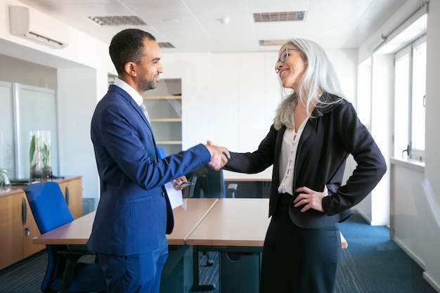 Confident partners handshaking or greeting in meeting room. successful content businessman and professional grey-haired manager concluding contract. teamwork, business and partnership concept Free Photo