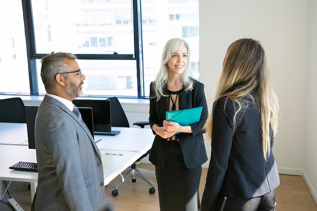 Уверенные партнеры встречаются в офисе, разговаривают и улыбаются. бородатый босс в очках обсуждает проект с красивыми женщинами-предпринимателями. концепция бизнеса, коммуникации и высшего руководства Бесплатные Фотографии
