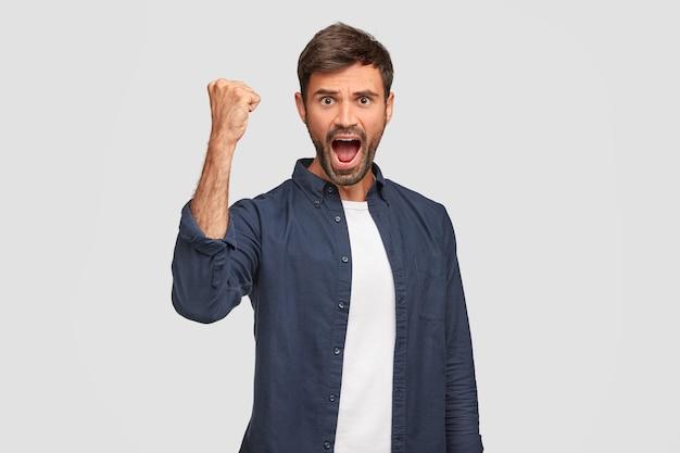 Уверенный и позитивный мужчина-победитель держит руку сжатой в кулак, широко раскрывает рот, торжественно восклицает, эмоционально, чувствует успех, стоит у белой стены. концепция достижения Бесплатные Фотографии