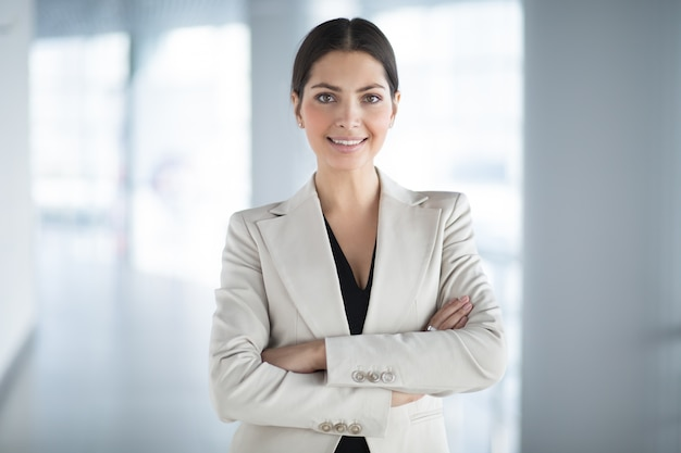 Confident pretty business woman with arms crossed Free Photo