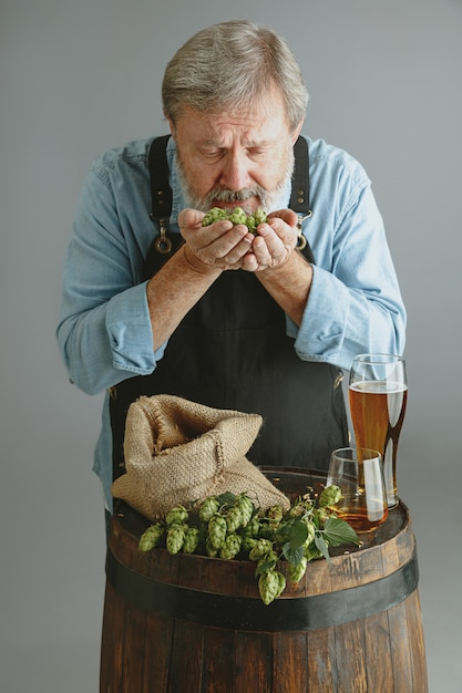 灰色の壁に木製の樽にガラスの自作ビールと自信を持って年配の男性醸造所 無料写真