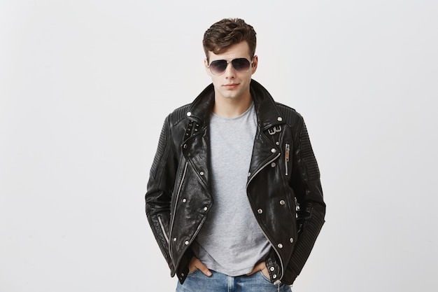 Confident serious handsome man wears black leather jacket over gray t-shirt and stylish eyewear, looks directly into camera, isolated . people and style concept Free Photo
