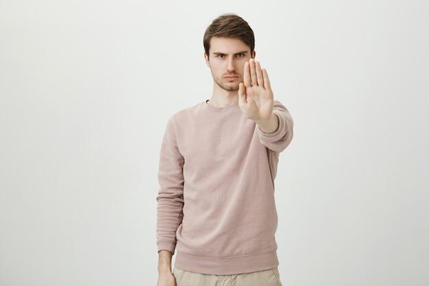 Уверенный серьезный мужчина протягивает руку, чтобы остановить, запретить или запретить действие Бесплатные Фотографии