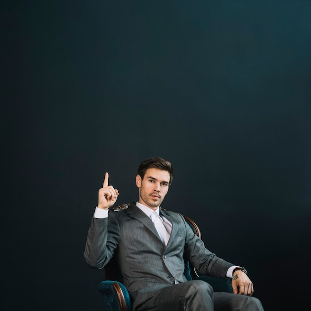 Confident smart young businessman sitting on armchair pointing finger upward against black background Free Photo
