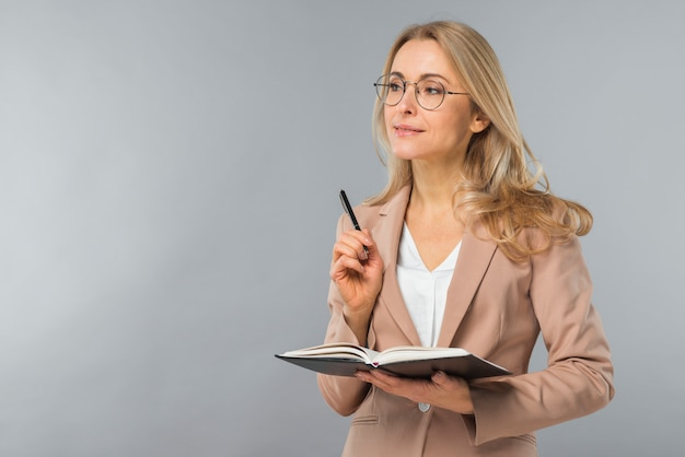 Confident smiling blonde young woman holding pen and diary in hand against gray background Free Photo