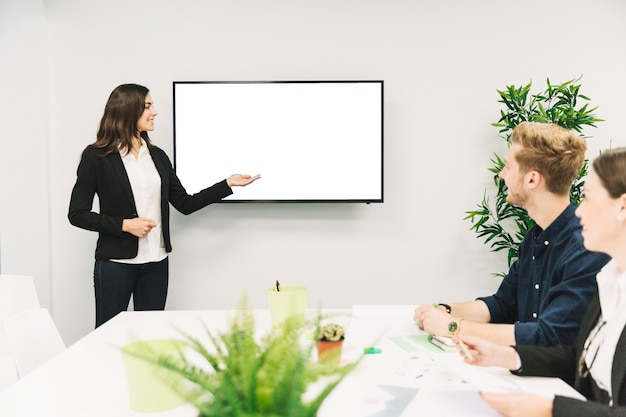 Confident smiling businesswoman giving presentation to her partners Free Photo