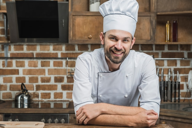 Confident smiling chef leaning on kitchen counter Free Photo