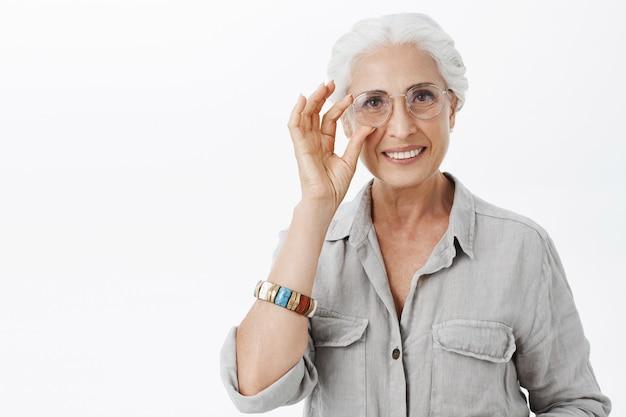 Уверенно улыбающаяся симпатичная старушка в очках, выглядящая довольной Бесплатные Фотографии