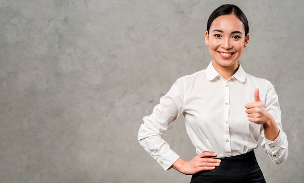 Confident smiling young businesswoman showing thumb up sign standing against grey wall Free Photo