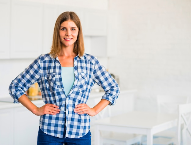 Confident smiling young woman standing in kitchen Free Photo