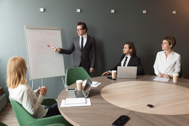 Confident speaker business coach gives presentation to team with flipchart Free Photo