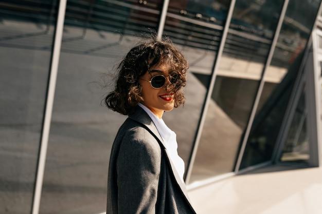 비즈니스 지구에서 산책하는 재킷을 입은 짧은 물결 모양의 머리를 가진 자신감 세련된 여성 무료 사진