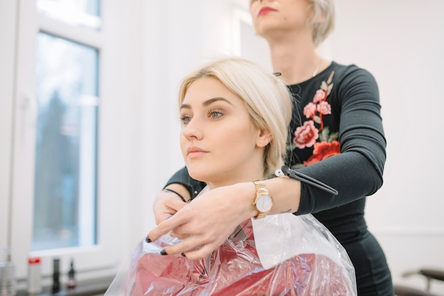 Confident stylist preparing young girl for haircut Free Photo