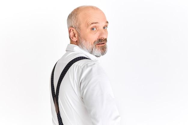 Уверенный успешный европейский мужчина на пенсии в стильной белой рубашке и подтяжках поворачивается и смотрит в камеру с серьезным выражением лица. люди, возраст, зрелость и концепция элегантности Бесплатные Фотографии