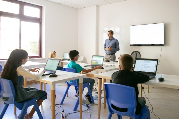 학생에게 수업을 설명하는 자신감있는 교사 무료 사진