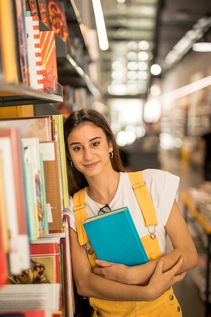 Confident teen schoolgirl with library book Free Photo