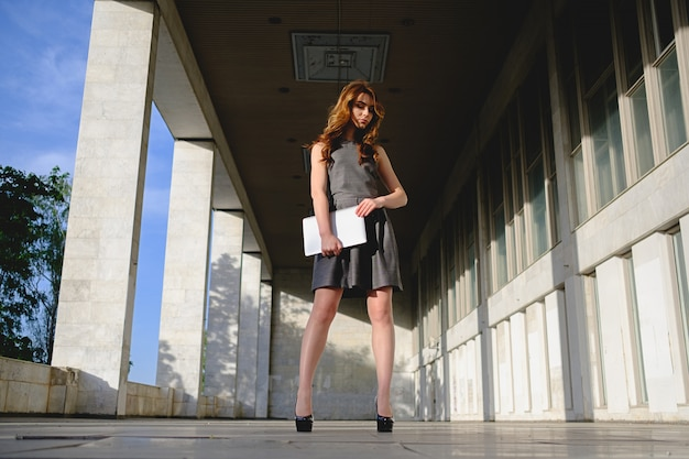 Confident woman holding a laptop Free Photo