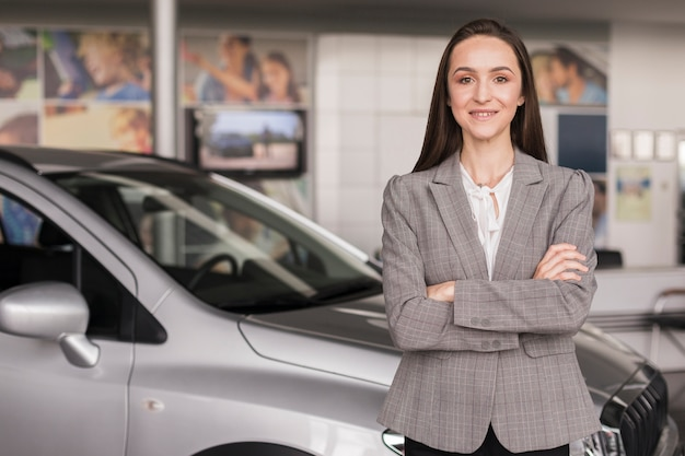 Confident woman posing in front of a car Free Photo