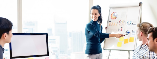 Confident woman pressenting financial chart in office meeting Premium Photo