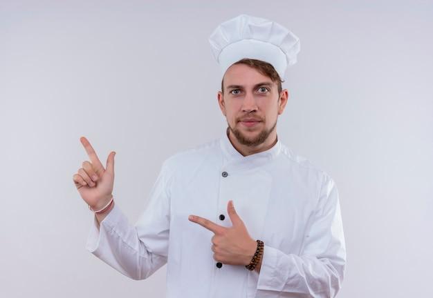 Un giovane uomo barbuto fiducioso del cuoco unico che indossa l'uniforme bianca del fornello e il cappello rivolto verso l'alto con le dita indice mentre guarda su una parete bianca Foto Gratuite