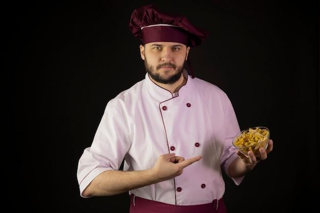 Уверенный молодой бородатый шеф-повар в униформе, указывая указательными пальцами на миску макарон в руке Premium Фотографии