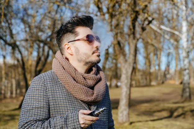 サングラスvape電子タバコで自信を持って若いひげを生やした男性。公園で屋外電子タバコを吸う若いハンサムなひげを生やした流行に敏感な男。閉じる。 Premium写真