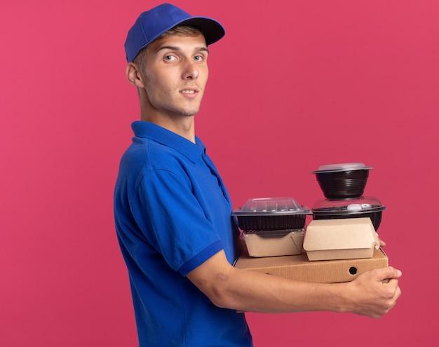 自信を持って若い金髪の配達の少年は、コピースペースとピンクの壁に分離されたピザボックスに食品容器とパッケージを保持して横に立っています 無料写真