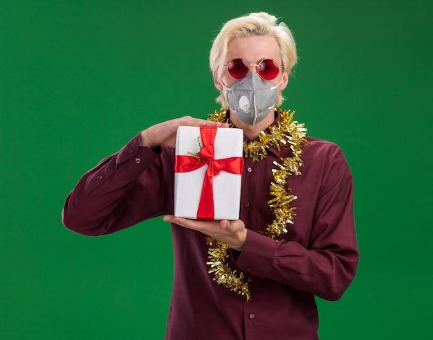 Fiducioso giovane uomo biondo con gli occhiali e maschera protettiva con la ghirlanda di tinsel intorno al collo che tiene il pacchetto regalo isolato sulla parete verde Foto Gratuite