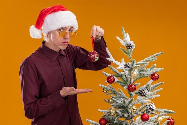 Fiducioso giovane uomo biondo che indossa santa cappello e occhiali in piedi in vista di profilo vicino albero di natale decorato su sfondo arancione Foto Gratuite