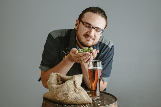 灰色の壁に木製の樽にガラスの自作ビールと自信を持って若い醸造所 無料写真