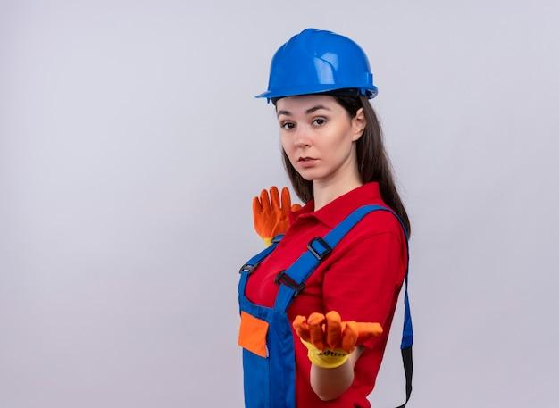 Fiduciosa giovane ragazza builder si leva in piedi lateralmente e tiene la mano su sfondo bianco isolato con spazio di copia Foto Gratuite