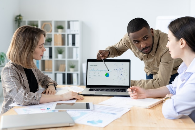 Уверенный молодой бизнесмен африканской национальности, глядя на одного из коллег, указывая на диаграмму на дисплее ноутбука Premium Фотографии
