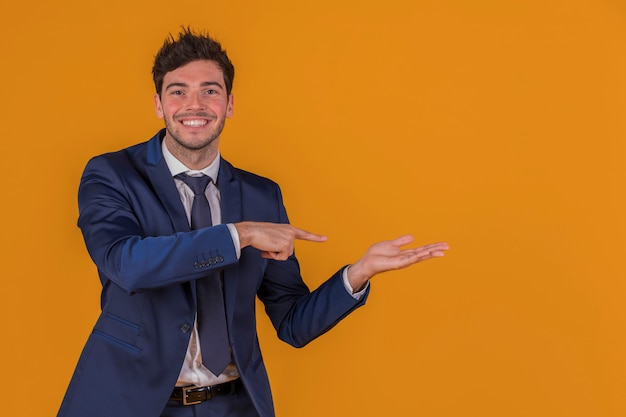 Confident young businessman pointing finger at something against an orange background Free Photo